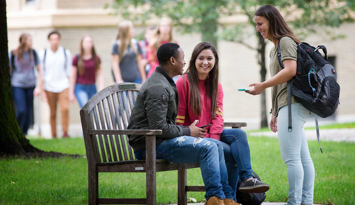 Students talking on a bench outside