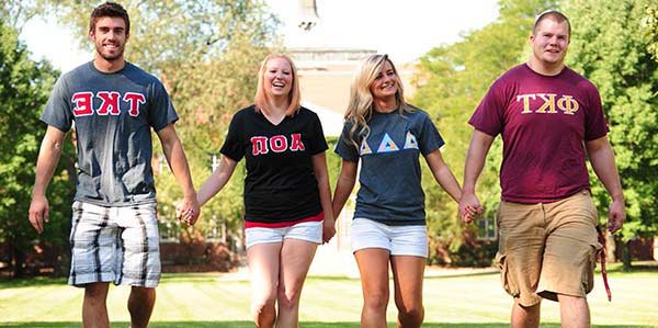 Fraternity men and sor要么ity women wearing their letters and holding hands as they walk across the quad